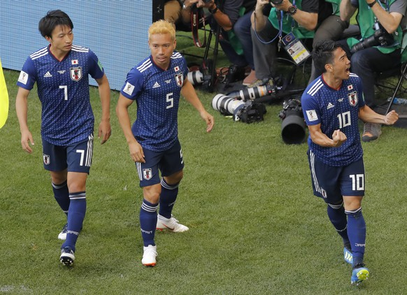 Japan's Shinji Kagawa, right, celebrates with Yuto Nagatomo, center, and Gaku Shibasaki, left, scoring opening goal with Japan's head coach Akira Nishino, left, during the group H match between Colombia and Japan at the 2018 soccer World Cup in the Mordavia Arena in Saransk, Russia, Tuesday, June 19, 2018. (AP Photo/Vadim Ghirda)