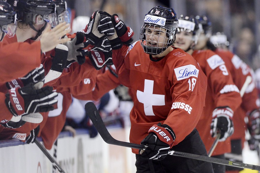 Switzerland forward Nico Hischier (18) celebrates with teammates at the bench after scoring against the United States during the third period of a quarterfinal hockey game at the world junior championship in Toronto, Monday, Jan. 2, 2017. (Frank Gunn/The Canadian Press via AP)