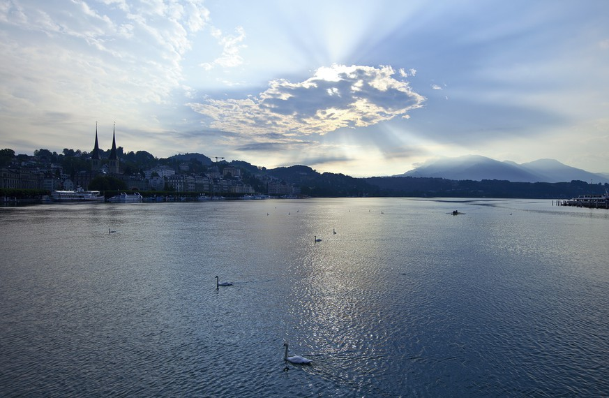 The sun hides behind a cloud above Lake Lucerne with