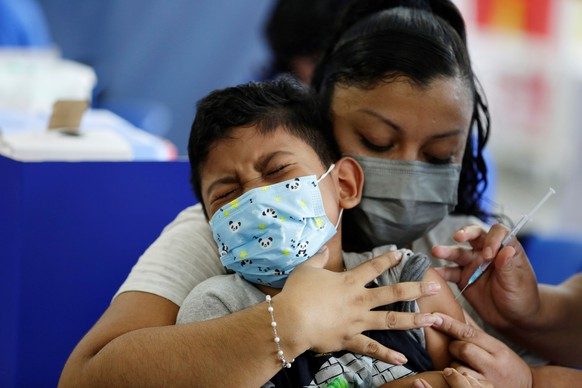 epa09482351 A child reacts as he receives the first dose of vaccine against Covid-19, at the vaccination center of Hospital El Salvador, in San Salvador, 22 September 2021. El Salvador began inoculating children between six and 11 years of age, amid a rise in Covid-19 cases in the country.  EPA/Rodrigo Sura
