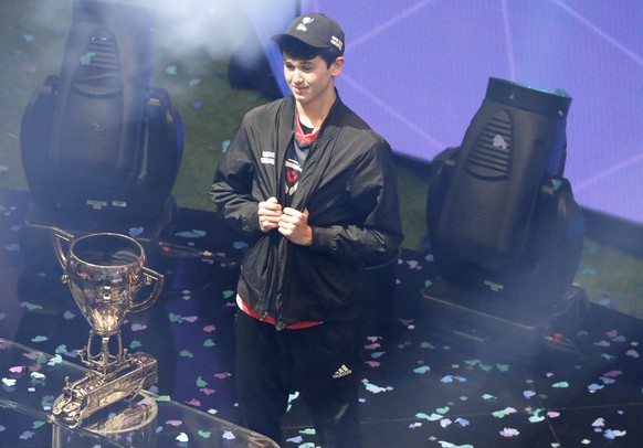 epaselect epa07746778 Fortnite player Bugha celebrates with the FortNite Championship Trophy after winning the finals of the Solo competition at the 2019 Fortnite World Cup at Flushing Meadows Arthur Ashe stadium in Queens, New York, USA, 28 July 2019.  EPA/JASON SZENES