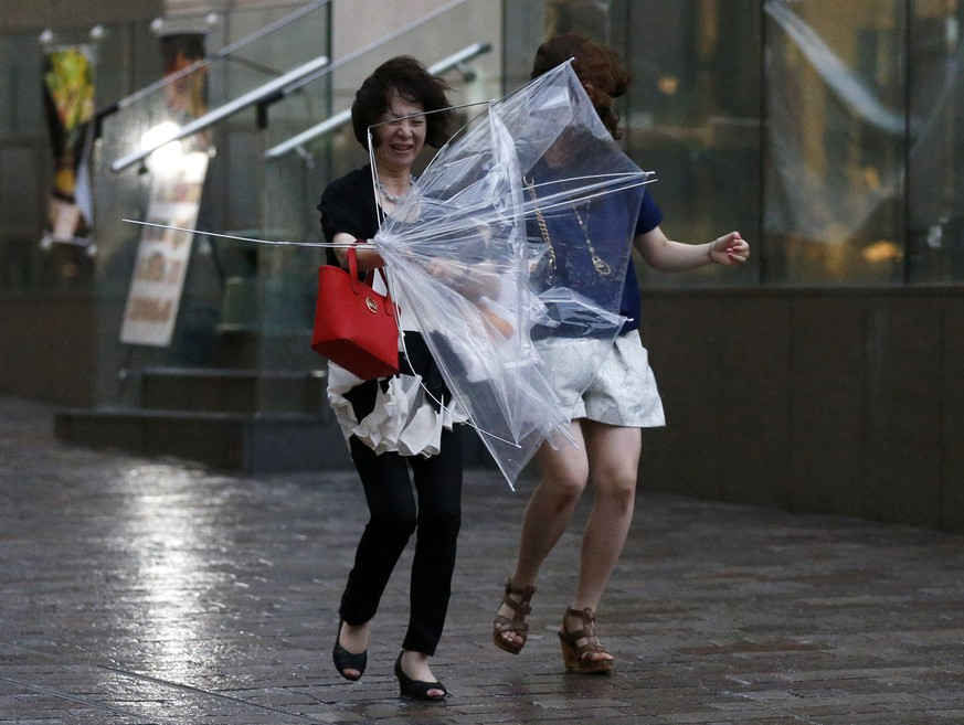 Women struggle with strong winds and rain caused by Typhoon Halong in Tokyo August 10, 2014. Typhoon Halong killed one person in Japan on Sunday and injured 33, media said, as authorities ordered 1.6 million people out of the path of the storm that battered the west of the country with heavy rain and wind.   REUTERS/Toru Hanai (JAPAN - Tags: ENVIRONMENT DISASTER)