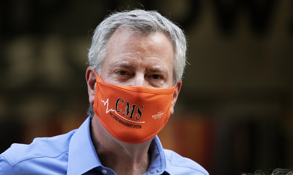 New York Mayor Bill de Blasio wears a mask while painting Black Lives Matter on Fifth Avenue in front of Trump Tower, Thursday, July 9, 2020, in New York. (AP Photo/Mark Lennihan)