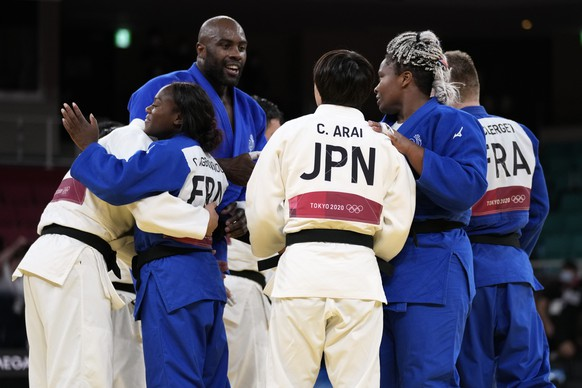 Members of the French team, in blue, and Japanese team shake hands after their gold medal match in team judo competition at the 2020 Summer Olympics, Saturday, July 31, 2021, in Tokyo, Japan. (AP Photo/Vincent Thian)
