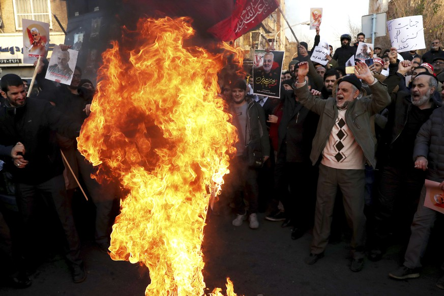 Protesters chant slogans and hold up posters of Gen. Qassem Soleimani while burning representations of British and Israeli flags, during a demonstration in front of the British Embassy in Tehran, Iran, Sunday, Jan. 12, 2020. A candlelight ceremony late Saturday in Tehran turned into a protest, with hundreds of people chanting against the country's leaders â?? including Supreme Leader Ayatollah Ali Khamenei â?? and police dispersing them with tear gas. Police briefly detained the British ambassador to Iran, Rob Macaire, who said he went to the Saturday vigil without knowing it would turn into a protest. (AP Photo/Ebrahim Noroozi)