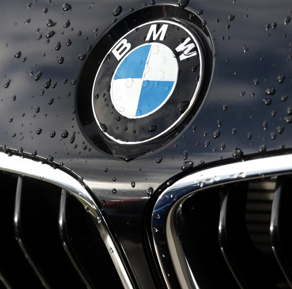 The company logo of car manufacturer BMW is pictured on a car in Munich, Germany, Tuesday, March 19, 2013. German luxury automaker BMW AG says earnings fell 28 percent in the second quarter due to higher costs for investments in new technology and personnel. A large one-time plus from the same quarter a year ago affected the comparison. (AP Photo/Matthias Schrader)