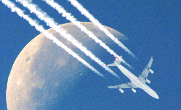 A north-west bound four-engine plane flies past the half moon,  leaving its contrails in the clear skies over Frankfurt, Germany, Monday morning, Sept. 30, 2002, as clear early autumn weather prevails over most parts of Germany with the moon easily visible almost all day. (AP Photo/Frank Rumpenhorst)
