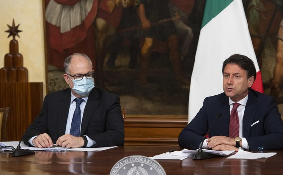 Italian Prime Minister, Giuseppe Conte, right, with Economy Minister Roberto Gualtieri, left, announces the latest set of measures under another emergency decree during the coronavirus pandemic, Friday, Aug. 7, 2020, in Rome, Italy. (Claudio Peri/Pool Photo via AP) Giuseppe Conte,Roberto Gualtieri