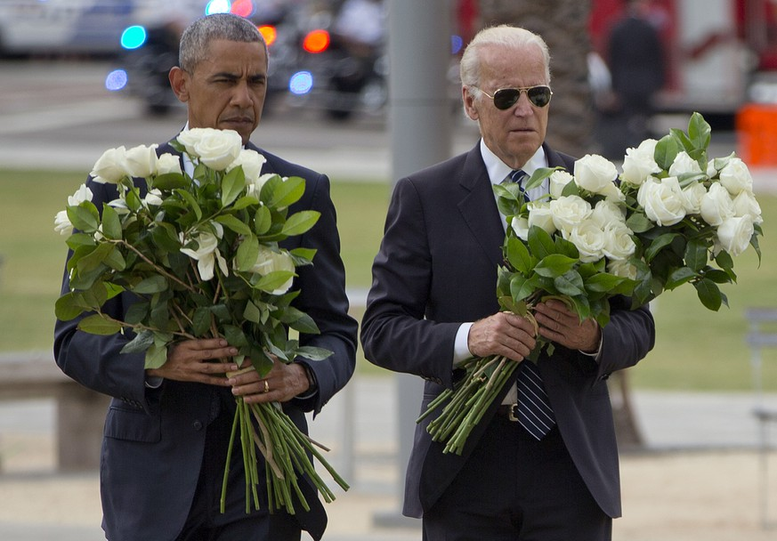 President Barack Obama with Vice President Joe Biden carry bouquets comprised of a total of 49 white roses, one in honor of each of the deceased victims, as they visit a memorial to the victims of the Pulse nightclub shooting, Thursday, June 16, 2016 in Orlando, Fla. Offering sympathy but no easy answers, Obama came to Orlando to try to console those mourning the deadliest shooting in modern U.S history. (AP Photo/Pablo Martinez Monsivais)