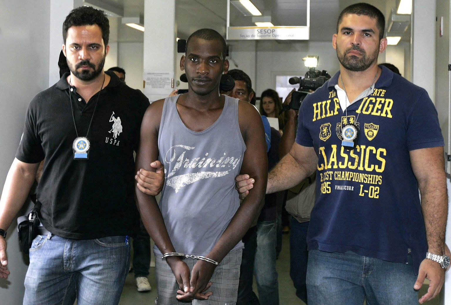 Sailson Jose das Gracas, 26, is escorted by policemen at a police station in Nova Iguacu near Rio de Janeiro December 11, 2014. Gracas, who was arrested on Wednesday, told reporters at a police station in the state of Rio that he killed for pleasure and the accompanying adrenaline rush. He said he also operated as a killer for hire. He said his preferred victims were white females, whom he strangled. Among the 42 victims, 39 are thought to be women.  REUTERS/Fabio Golcalves/Agencia O Dia (BRAZIL - Tags: CRIME LAW TPX IMAGES OF THE DAY)