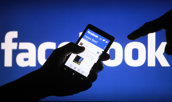 A smartphone user shows the Facebook application on his phone in the central Bosnian town of Zenica, in this file photo illustration taken May 2, 2013.  Facebook Inc's mobile advertising business continued to accelerate in the first three months of the year, helping the Internet social networking company top Wall Street's revenue target.  REUTERS/Dado Ruvic/Files  (BOSNIA AND HERZEGOVINA - Tags: BUSINESS)