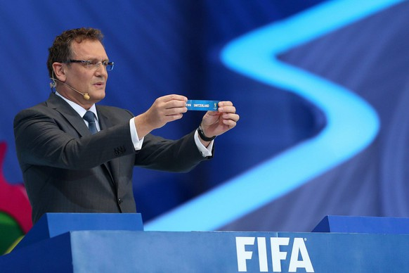 epa03979794 General Secretary of FIFA Jerome Valcke shows the ballot with the name of Switzerland during the final draw of the preliminary round groups of the 2014 FIFA World Cup Brazil in Costa do Sauipe, Brazil, 06 December 2013.  EPA/MARCELO SAYAO