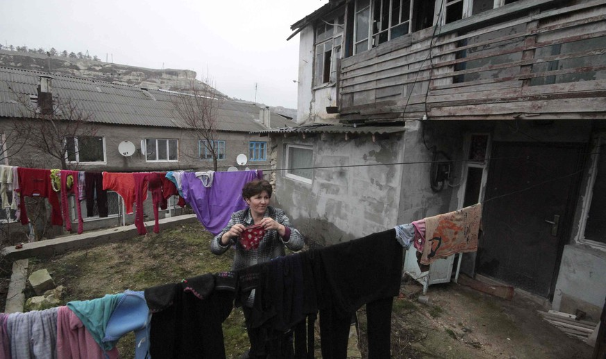 A woman hangs out the laundry near her house in Bakhchisaray's Old Town March 13, 2015. REUTERS/Pavel Rebrov (CRIMEA - Tags: SOCIETY)
