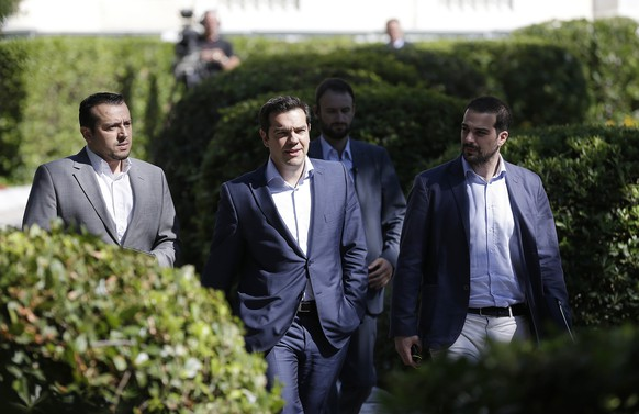 Greece's Prime Minister Alexis Tsipras, center, leaves after a meeting with leaders of Greek political parties at the Presidential Palace in Athens, Monday, July 6, 2015. Greece and its membership in Europe's joint currency faced an uncertain future Monday, with the country under pressure to reach a bailout deal with creditors as soon as possible after Greeks resoundingly rejected the notion of more austerity in exchange for aid. (AP Photo/Petr David Josek)