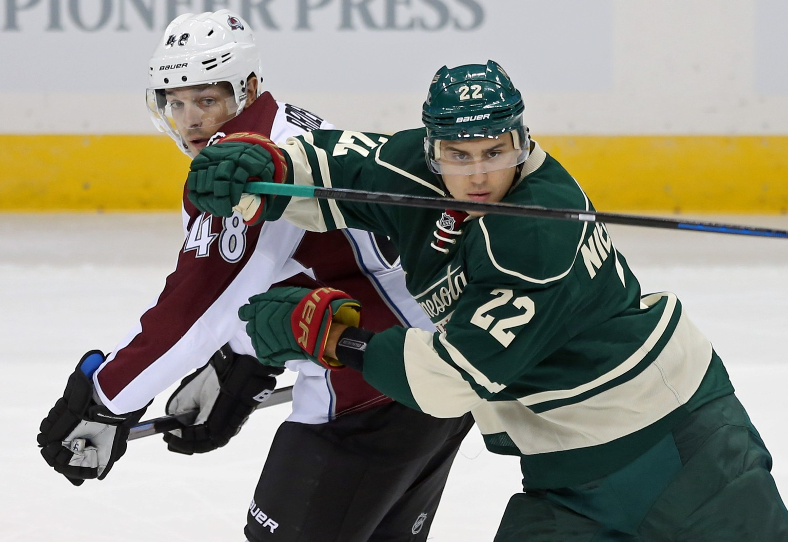 Minnesota Wild's Nino Niederreiter, right, of Switzerland, eyes the puck as he tries to keep Colorado Avalanche' s Daniel Briere at bay in the first period of an NHL hockey game, Thursday, Oct. 9, 2014, in St. Paul, Minn. (AP Photo/Jim Mone)