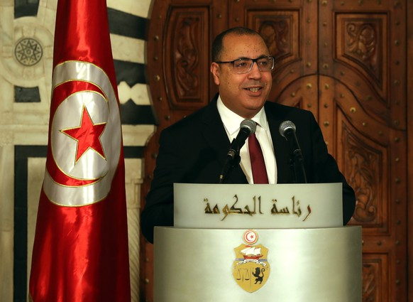 epa08942174 Tunisian Prime Minister Hichem Mechichi speaks to the media during a press conference to announce a cabinet reshuffle in Tunis, Tunisia, 16 Janury 2021. Tunisian Prime Minister Hichem Mechichi announced on 16 January 2021, the appointment of 12 new Ministers in a cabinet reshuffle, that he hopes will ease the rising political tensions and help with the unprecedented economic crisis.  EPA/MOHAMED MESSARA