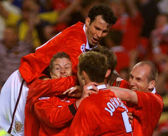 Manchester United's Ole Gunnar Solskjaer (bottom left) is mobbed by his temmates Ryan Giggs (top), Ronny Johnsen (center) and Jaap Stam after scoring the winning goal in the UEFA Champions League final at the Nou Camp Stadium in Barcelona on Wednesday, May 26, 1999. United beat Bayern Munich 2-1. (KEYSTONE/AP Photo/PA/Owen Humphreys)         === ELECTRONIC IMAGE .UNITED KINGDOM OUT. MAGAZINES OUT.  ===