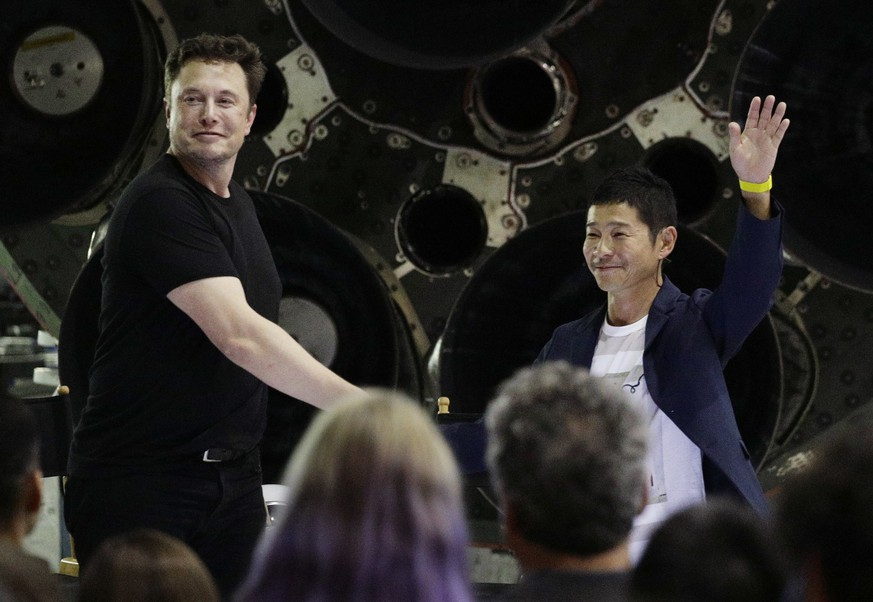 SpaceX founder and chief executive Elon Musk, left, shakes hands with Japanese billionaire Yusaku Maezawa, right, after announcing him as the first private passenger on a trip around the moon, Monday, Sept. 17, 2018, in Hawthorne, Calif. (AP Photo/Chris Carlson)