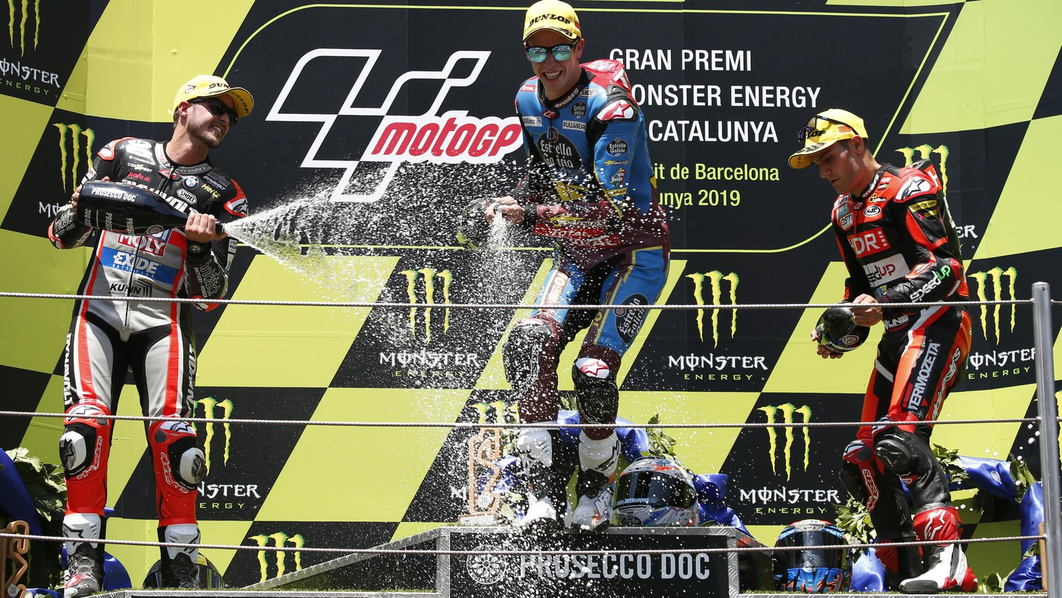 Moto2 race winner Alex Marquez of Spain, center, celebrates with 2nd placed Thomas Luthi of Switzerland, left and 3rd placed Jorge Navarro of Spain during the Catalunya Motorcycle Grand Prix at the Barcelona Catalunya racetrack in Montmelo, near Barcelona, Spain, on Sunday June 16, 2019. (AP Photo/Joan Monfort)
