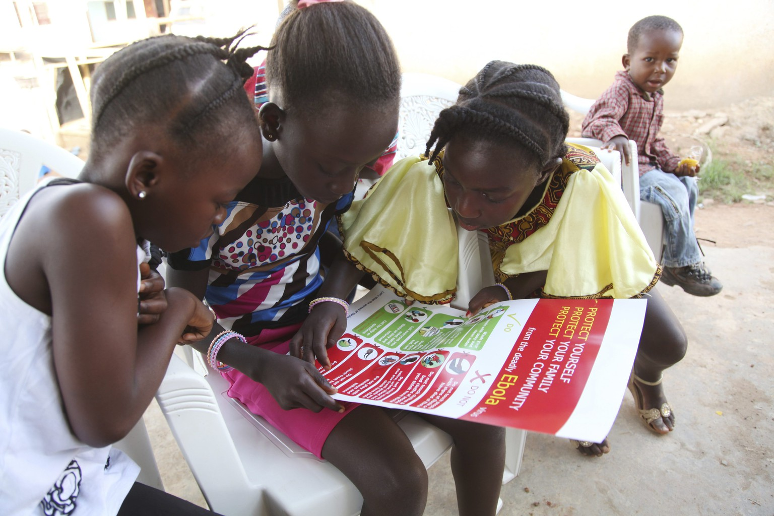 Girls look at a poster, distributed by UNICEF, bearing information on and illustrations of best practices that help prevent the spread of Ebola virus disease (EVD), in the city of Voinjama, in Lofa County, Liberia in this April 2014 UNICEF handout photo.  As of July 27, 2014, a total of 1,323 cases, including 729 deaths, had been attributed to EVD in the four West African countries of Guinea, Liberia, Nigeria and Sierra Leone. Liberia has borne 329 of these cases, including 156 deaths.  REUTERS/Ahmed Jallanzo/UNICEF/Handout via Reuters  (LIBERIA - Tags: HEALTH) THIS IMAGE HAS BEEN SUPPLIED BY A THIRD PARTY. IT IS DISTRIBUTED, EXACTLY AS RECEIVED BY REUTERS, AS A SERVICE TO CLIENTS. FOR EDITORIAL USE ONLY. NOT FOR SALE FOR MARKETING OR ADVERTISING CAMPAIGNS. MANDATORY CREDIT