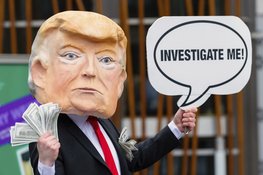 IMAGE DISTRIBUTED FOR AVAAZ - A member of the global citizens movement Avaaz wearing a mask of former US President Donald Trump holds a sign reading