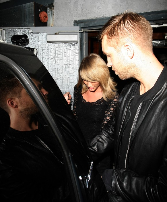 Mobbed by photographers and fans singer Taylor Swift and her rumored boyfriend Calvin Harris leaving Troubadour club holding hands, in West Hollywood,CA