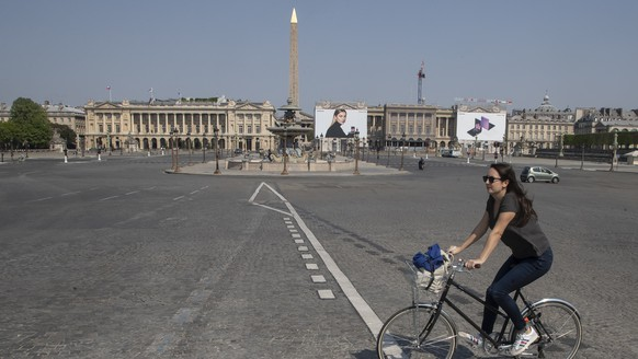 A woman crosses the Concorde square as she rides a bike during a nationwide confinement to counter the new coronavirus. in Paris, Friday, April 10, 2020. For most people, the new coronavirus causes only mild or moderate symptoms, such as fever and cough. For some, especially older adults and people with existing health problems, it can cause more severe illness, including pneumonia. (AP Photo/Michel Euler)