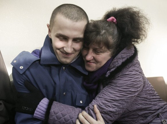 epa04540544 An Ukrainian woman hugs her son, who was a prisoner of war, as pro-Russian rebels released him in Luhansk, Ukraine, 26 December 2014. Three Ukrainian prisoners of war were dismissed without any conditions and handed to their relatives by representatives of Luhansk People's Republic (LNR) on 26 December.  EPA/YURIY STRELTSOV