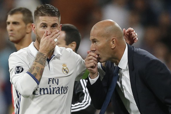 Real Madrid's head coach Zinedine Zidane gives tactical advise to Real Madrid's Sergio Ramos during a Champions League, Group F soccer match between Real Madrid and Sporting, at the Santiago Bernabeu stadium in Madrid, Spain, Wednesday, Sept. 14, 2016. (AP Photo/Daniel Ochoa de Olza)