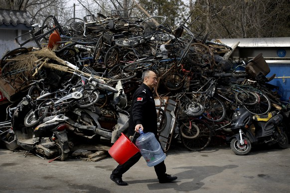 A security guard walks past a pile of abandoned bicycles and electric bikes which collected by cleaners placed near a garbage recycling center in Beijing, Thursday, Feb. 25, 2016. (AP Photo/Andy Wong)