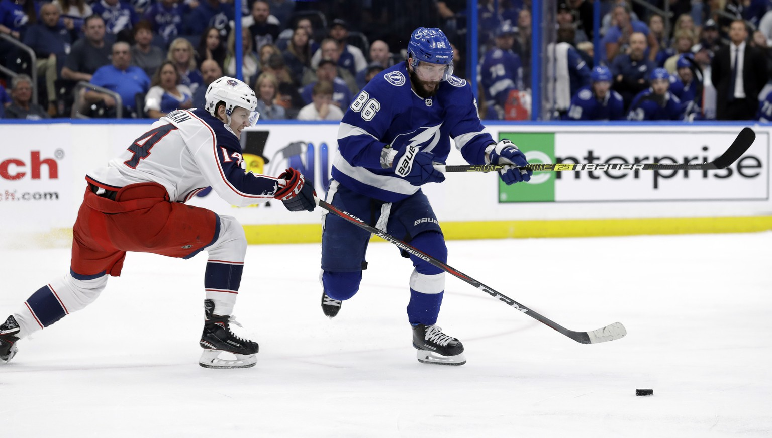 Columbus Blue Jackets defenseman Dean Kukan (14) tips the puck away from Tampa Bay Lightning right wing Nikita Kucherov (86) during the second period of Game 1 of an NHL Eastern Conference first-round hockey playoff series Wednesday, April 10, 2019, in Tampa, Fla. (AP Photo/Chris O'Meara)
