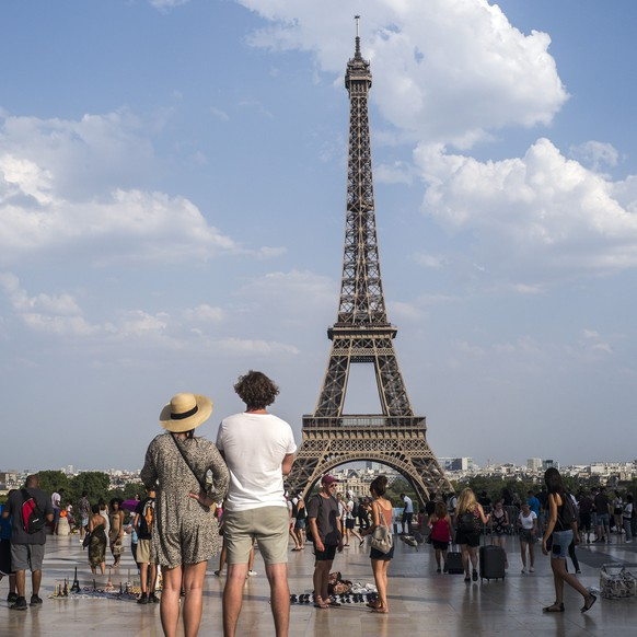 People stand in the sun and look at the Eiffel Tower in Paris, Thursday July 25, 2019, when a new all-time high temperature of 42.6 degrees Celsius (108.7 F) hit the French capital. (AP Photo/Rafael Yaghobzadeh)