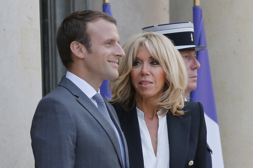 French President Emmanuel Macron, left, his wife Brigitte Macron await Belgian Prime Minister Charles Michel and Luxembourg Prime Minister Xavier Bettel for a diner at the Elysee Palace in Paris, France, Thursday, July 20, 2017. (AP Photo/Michel Euler)