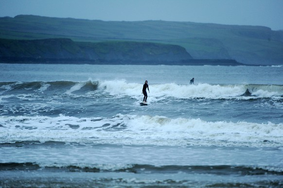 epa06267820 A woman surfing on Lahinch Strand in County Clare, Ireland, 15 October 2017, prior of the arrival of Storm Ophelia which will hit the west coast of Ireland along the Atlantic seaboard on 16 October 2017. The Hurricane Ophelia has been downgraded to a storm but will still be the largest storm to hit Ireland in over 50 years.  EPA/Aidan Crawley