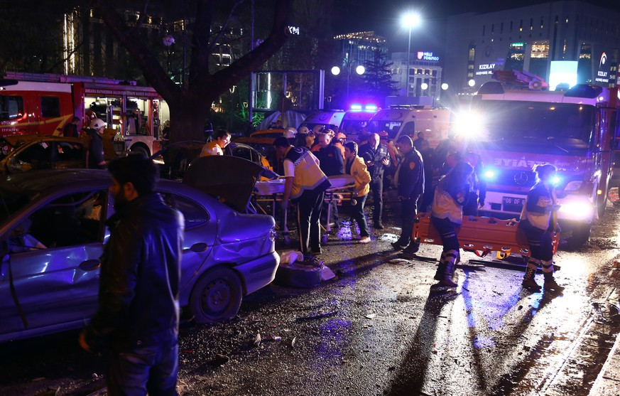 Medics and security members at the explosion site in the busy center of Turkish capital, Ankara, Turkey, Sunday, March 13, 2016. The explosion is believed to have been caused by a car bomb that went off close to bus stops. News reports say the large explosion in the capital has caused several deaths and many casualties. (AP Photo)