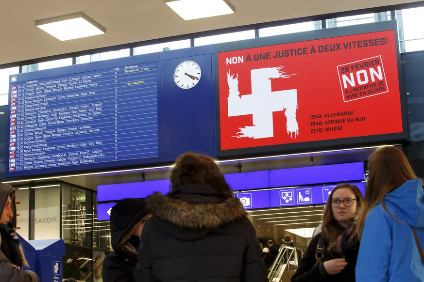 epa05179685 A photo made available 25 February 2016 shows a political advert (R), a montage of the white cross of the Swiss national flag and the Swastika symbol, at the SBB train station Cornavin in Geneva, Switzerland, on 23 February 2016. A initiative launched by Swiss People's Party SVP seeking to enforce the deportation of convicted foreigners ('Enforcement Initiative') is one of four separate issues Swiss voters will decide in the nationwide ballot on 28 February 2016.  EPA/SALVATORE DI NOLFI