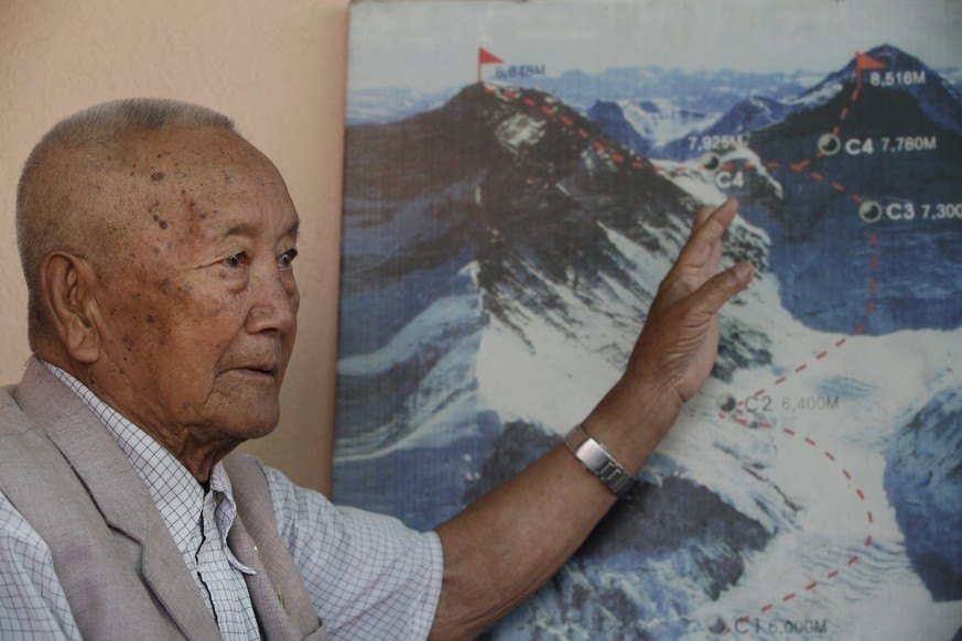 In this Tuesday, April 11, 2017 photo, Nepalese climber Min Bahadur Sherchan, points to a picture to describe the trail to Mount Everest, as he talks to Associated Press at his residence in Kathmandu, Nepal. The 85-year-old climber who was once the oldest person to scale the world's highest mountain is heading back to Mount Everest in hopes of scaling the peak and regaining the title. Sherchan is aiming to scale the peak next month when there is window of favorable weather on the summit. (AP Photo/Niranjan Shrestha)