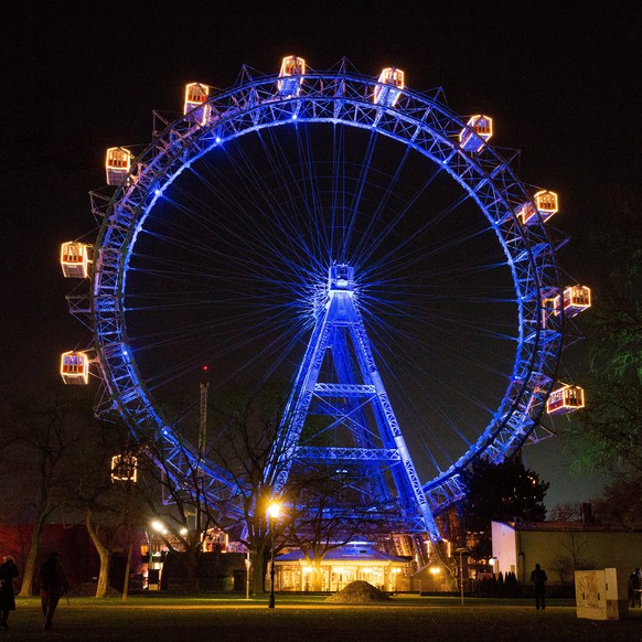 epa06371863 The Giant Ferris Wheel (Wiener Riesenrad) in the Prater park is illuminated in Finland's blue and white colors to celebrate Finland's intependence centenary in Vienna, Austria, 06 December 2017.  EPA/LISI NIESNER