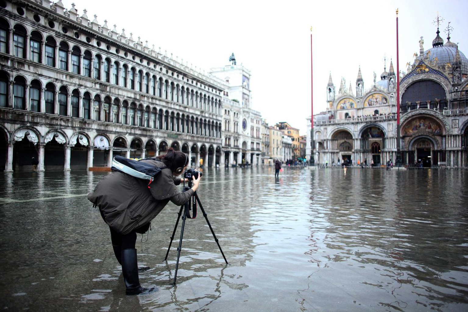 epa03488906 A tourist takes a picture in a flooded San Marco Square, Venice, Italy, 28 November 2012. In Venice, authorities were cautiously hopeful that the high water, which had reached 103 centimetres, will be lower than earlier forecast. Waters were flooding about 10 per cent of the historic city's centre, lifted higher still by the force of sirocco winds. Italy has set up weather alerts in Tuscany and in other areas of northern Italy.  EPA/ANDREA MEROLA