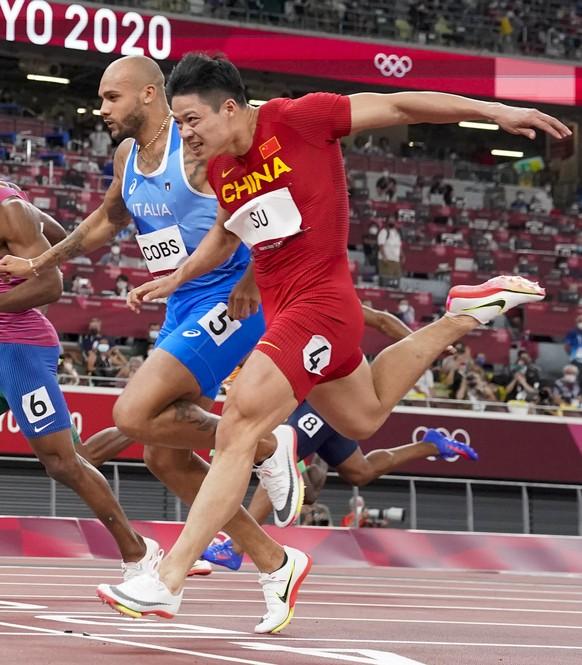 Su Bingtian, of China, right, wins a men's 100-meter semifinal at the 2020 Summer Olympics, Sunday, Aug. 1, 2021, in Tokyo. (AP Photo/David J. Phillip)