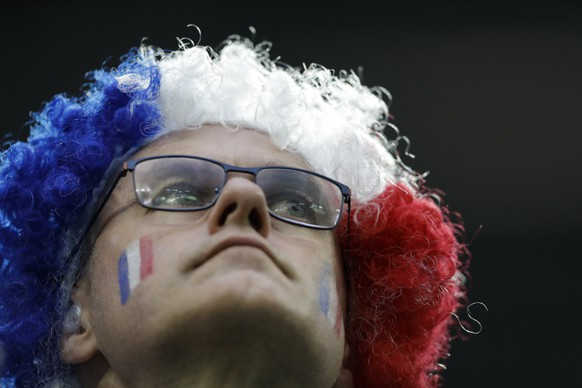 A French fan wear a tricolour wig in the national colours of France as he looks out from the stands before the start of the semifinal match between France and Belgium at the 2018 soccer World Cup in the St. Petersburg Stadium in, St. Petersburg, Russia, Tuesday, July 10, 2018. (AP Photo/Natacha Pisarenko)