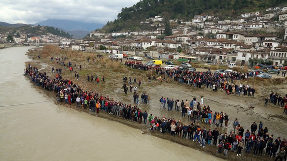 View of the people gathered  in the southern city of Berat to watch an Eastern Orthodox priest throw a cross in the Osum River to celebrate Epiphany day as people believe that the one who retrieves it will be healthy through the year, Wednesday, Jan. 6, 2016. Albania is known for its religious coexistence where the Orthodox and Catholic communities live in peace with the majority Muslims.  (AP Photo/Hektor Pustina)