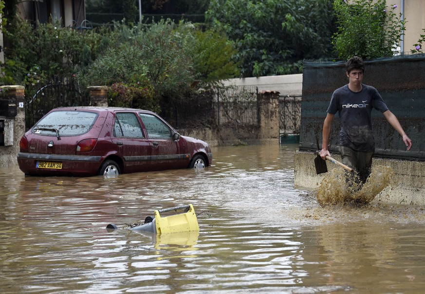 A man walks in a flooded street on September 18, 2014, in Lamalou-les-Bains, southern France. Four people died when storms turned a peaceful river that bordered their camping site in southern France into a raging torrent that swept them away, rescue workers said on September 18. The site in Lamalou-les-Bains was devastated by the flood overnight as storms that had already killed an elderly lady in the nearby region of Aveyron also left a person missing in another neighbouring department.  AFP PHOTO / PASCAL GUYOT