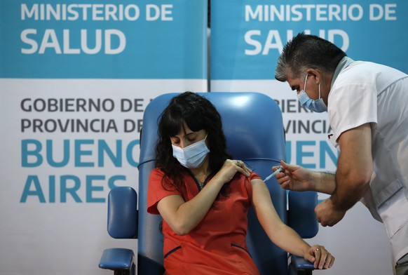 Nurse Gustavo Rodriguez gives Dr. Estefania Zevrnja a shot of Russia's Sputnik V vaccine for COVID-19 at Dr. Pedro Fiorito Hospital in Avellaneda, Argentina, Tuesday, Dec. 29, 2020. (AP Photo/Natacha Pisarenko)