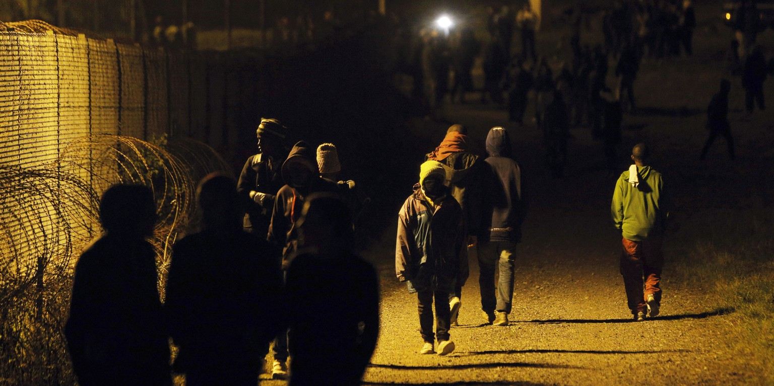 Migrants walk along a fence outside the Eurotunnel area, in Calais, northern France, Wednesday, July 29, 2015. Migrants rushed the tunnel linking France and England repeatedly for a second night on Wednesday and one man was crushed by a truck in the chaos, deepening tensions surrounding the thousands of people camped in this northern French port city. (AP Photo/Thibault Camus)