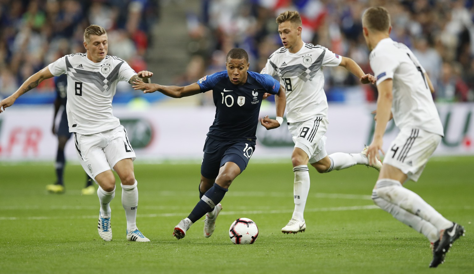 France's Kylian Mbappe, 2nd left, challenges for the ball with Germany's Toni Kroos, left, and Germany's Toni Kroos while Germany's Matthias Ginter, right, looks on during a UEFA Nations League soccer match between France and Germany at Stade de France stadium in Saint Denis, north of Paris, Tuesday, Oct. 16, 2018. (AP Photo/Christophe Ena)