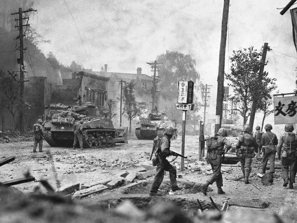 Smoke rises over debris-littered streets as tanks lead U.N. forces in the recapture of Seoul, Korea, Sept. 28, 1950. (AP Photo/Max Desfor)