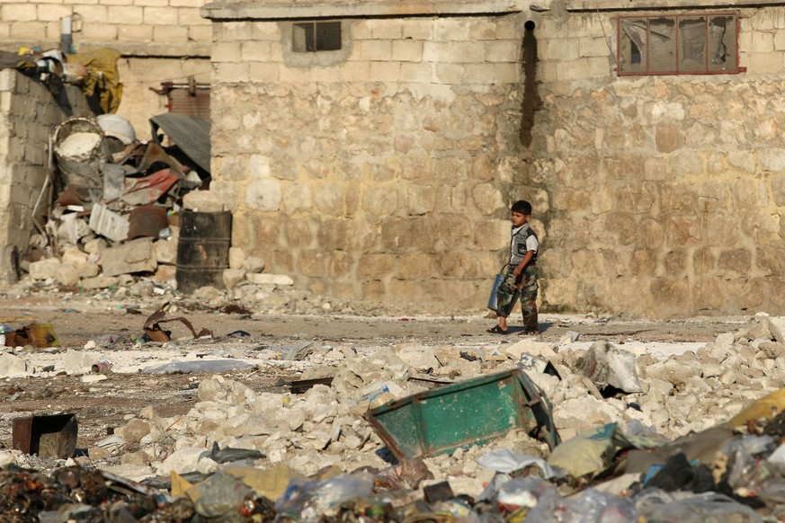 A boy walks past garbage and debris in the rebel-held al-Sheikh Said neighbourhood of Aleppo, Syria September 1, 2016. REUTERS/Abdalrhman Ismail