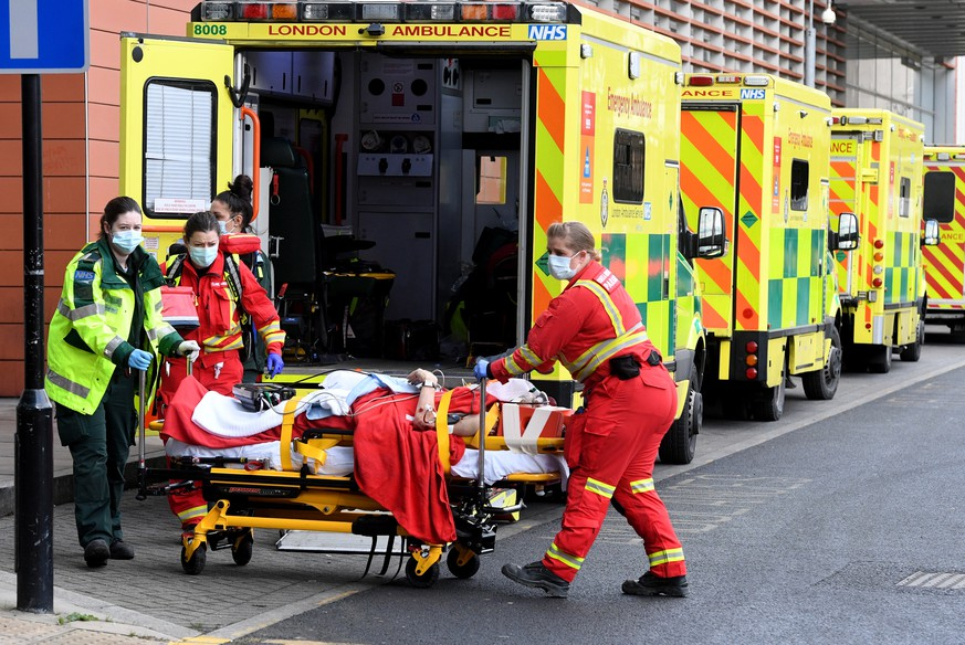 epa08916748 Ambulance workers assist a patient outside the Royal London Hospital in London, Britain, 03 January 2021. Coronavirus cases are continuing to surge across England with hospital admissions reaching new highs. More Covid patients tare now being treated in England than during the first wave in April.  EPA/FACUNDO ARRIZABALAGA