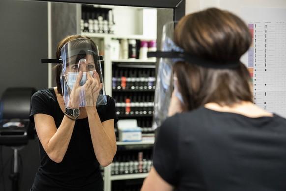 Susanne Heidegger, Inhaberin des Coiffeursalons Gallery Hairstyle, zieht eine Schutzmaske an, am Montag, 27. April 2020 in Bern. Coiffeure duerfen ihre Geschaefte ab heute wieder oeffnen. (KEYSTONE/Peter Klaunzer)